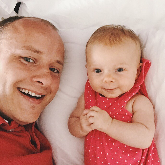 A father and child lat on the bed taking a selfie