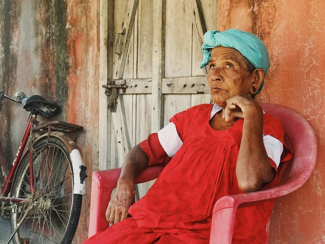 A blind woman sat down in a chair wearing a green headscarf and red dress