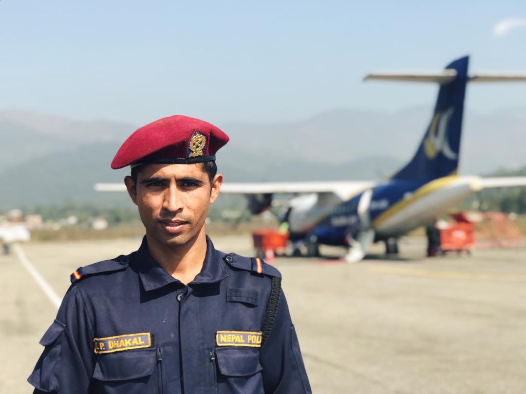 A police man standing in front of a plane
