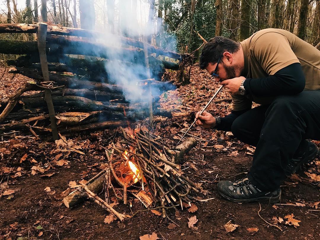 A man blowing air through a pocket bellows into a campfire