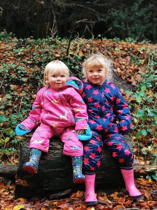 Two girls sat on a log in colourful all in ones and wellies.