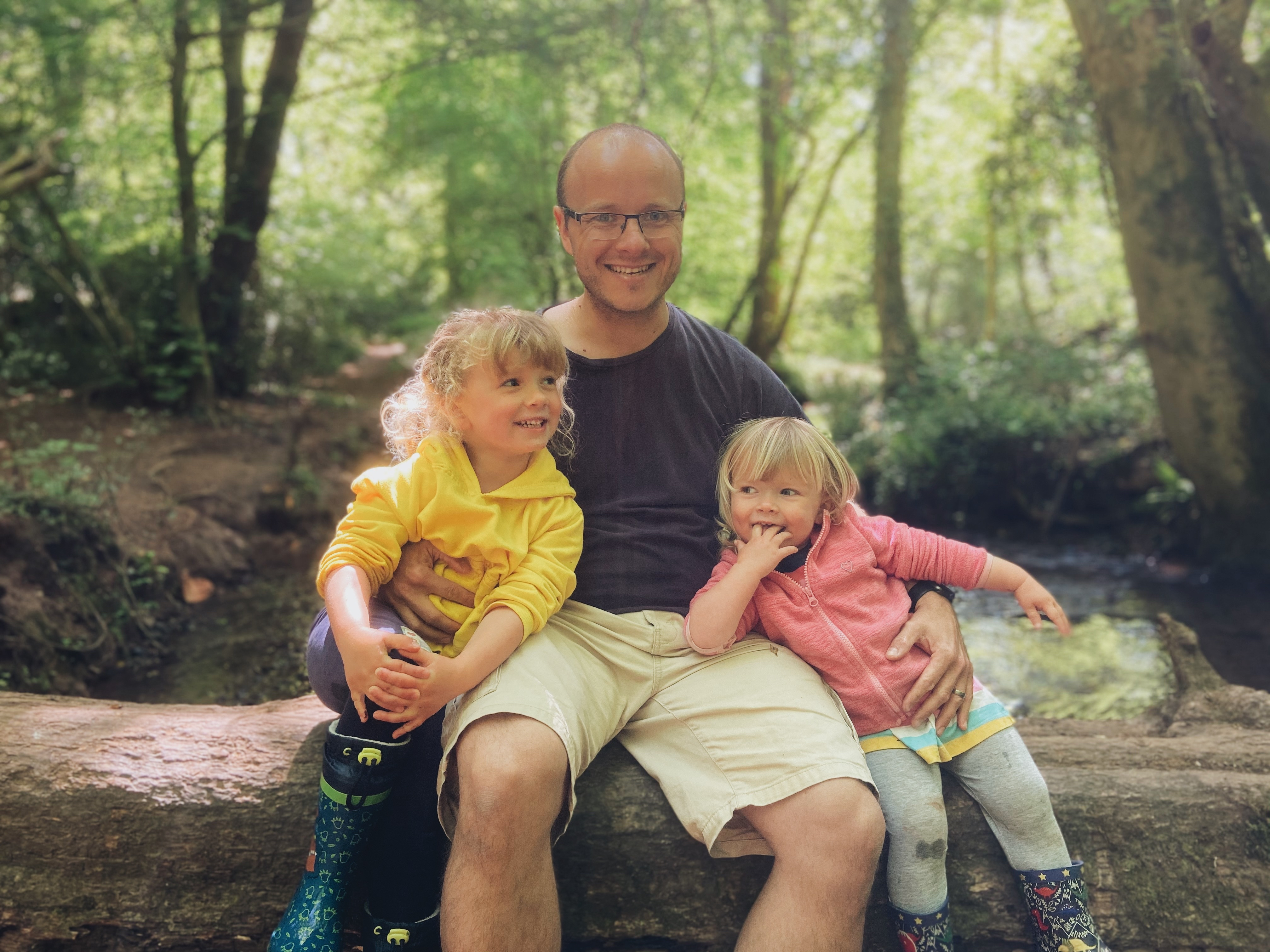 A dad and two girls sat on a log over a stream