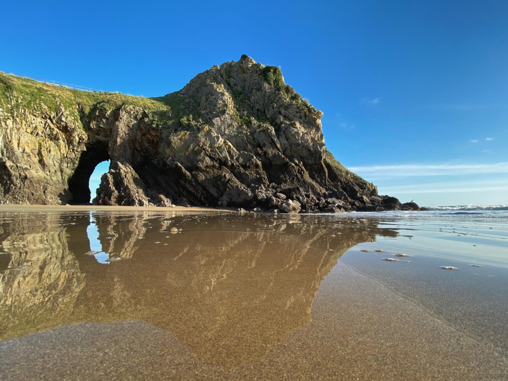 Caldey island reflected in the sand on a beach