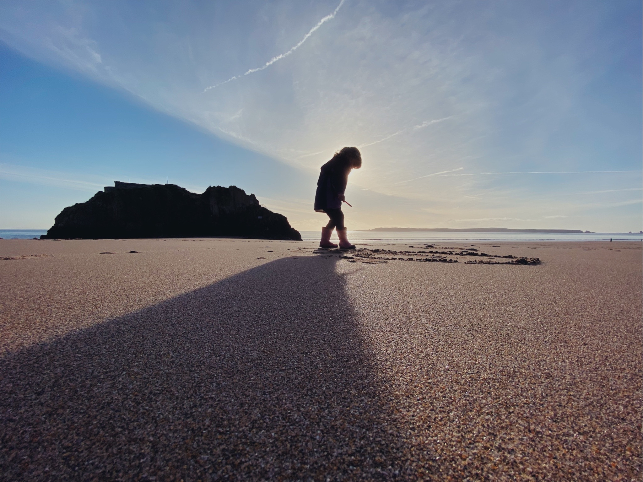 A little girl playing on the beach in silhouette with Caldey island in the background